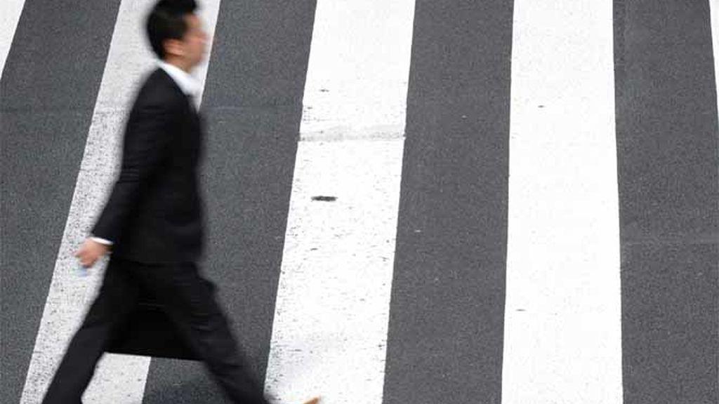 Peatón cruzando un paso de cebra en Tokio