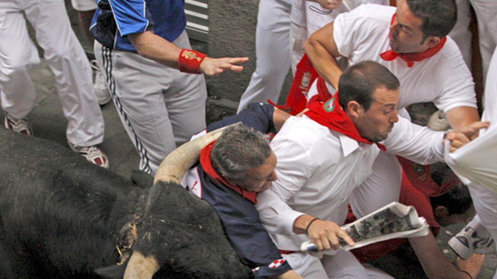 Dos personas a punto de ser corneadas por el toro
