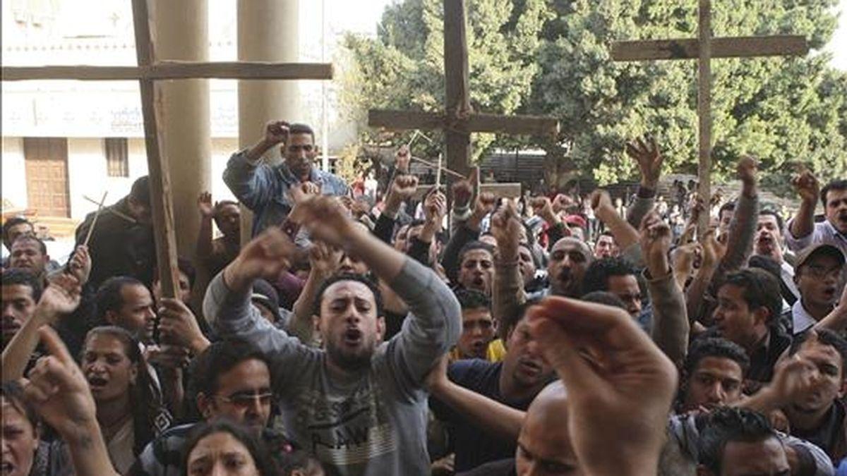 Unos cristianos coptos egipcios se manifiestan en el exterior de la catedral Abassya en El Cairo (Egipto) durante la reunión en la que el gran jeque de Al Azhar, Ahmed el-Tayeb, mantuvo hoy con el líder de la Iglesia copta, el papa Shenuda III, para presentarle sus condolencias por el atentado suicida de hace dos días en la iglesia de los Santos de Alejandría, que costó la vida a unos 21 personas y causó heridas a un centenar de ellas. EFE