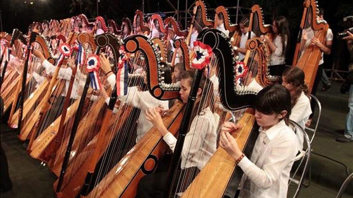 Un grupo de arpistas se presenta ante la sede del Cabildo en Asunción (Paraguay). El país comenzó anoche con un colorido espectáculo audiovisual, artístico y pirotécnico las celebraciones del Bicentenario de su Independencia. EFE