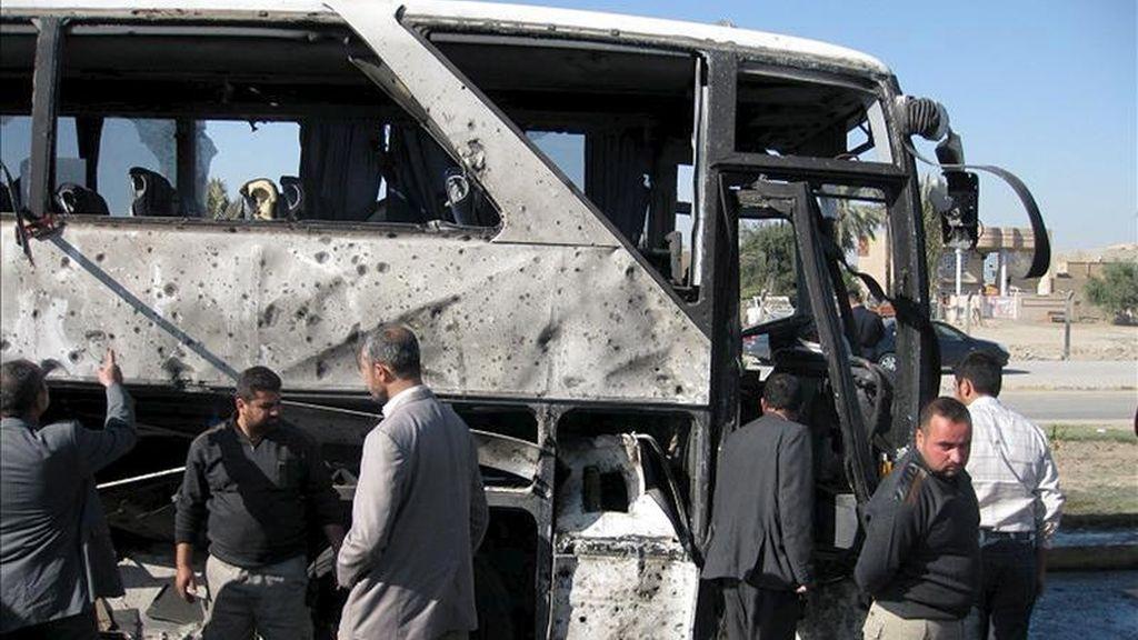 Iraquíes inspeccionan los restos de un autobús objeto de un atentado en Bagdad. EFE/Archivo