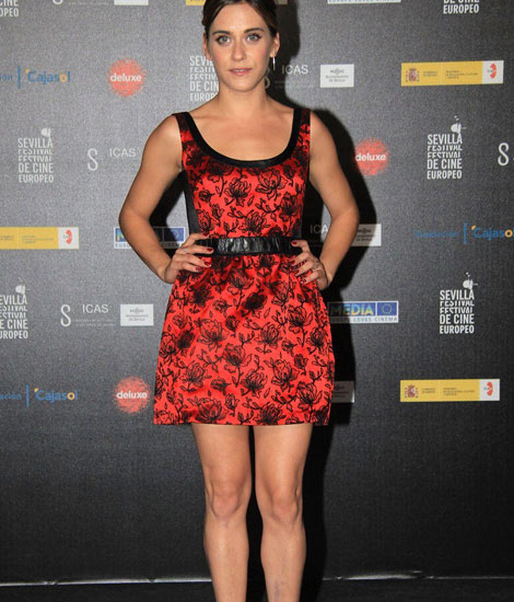 María León, de corto con vestido rojo de flores y complementos negros