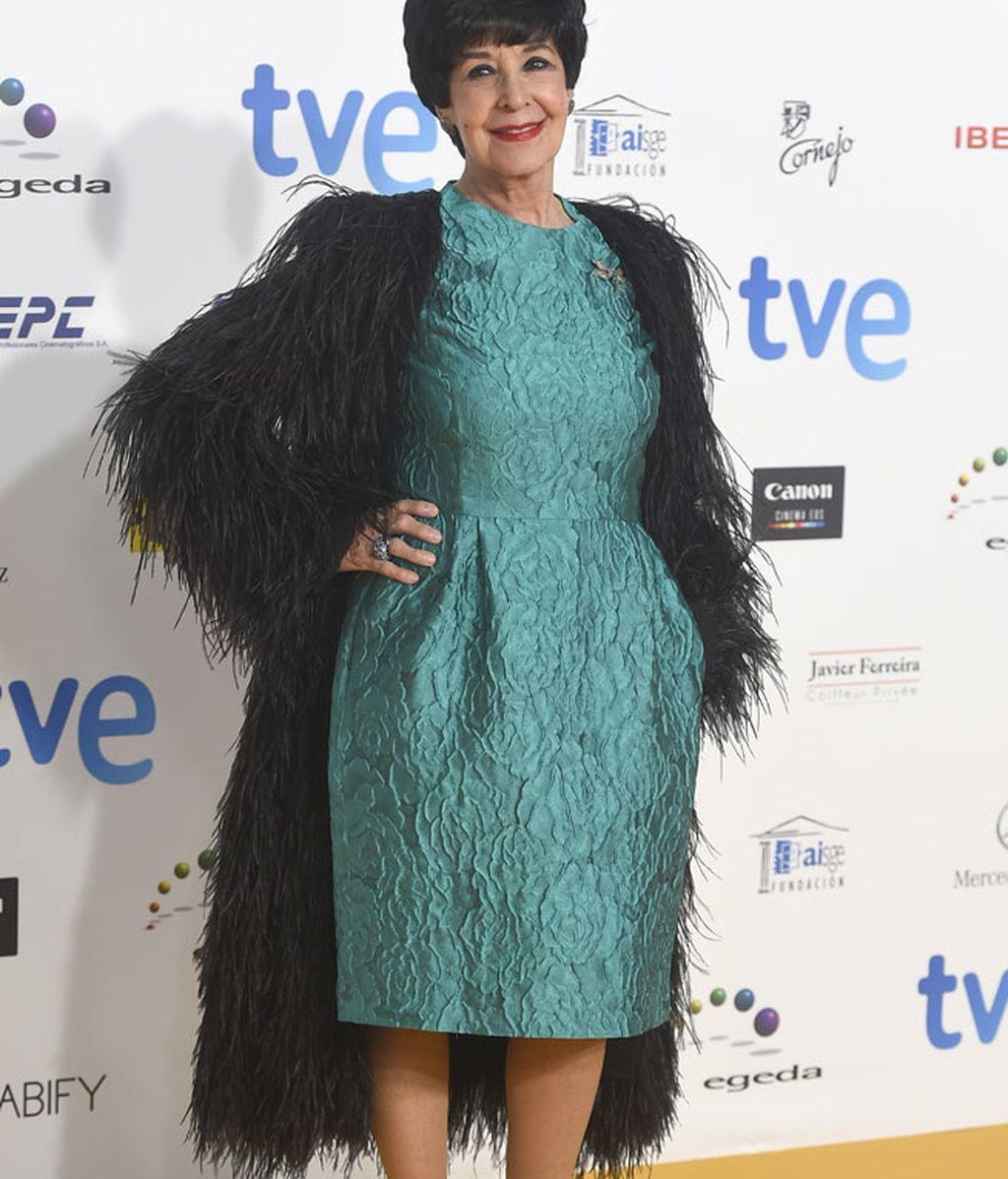 Concha Velasco con vestido de tela brocada y abrigo de plumas