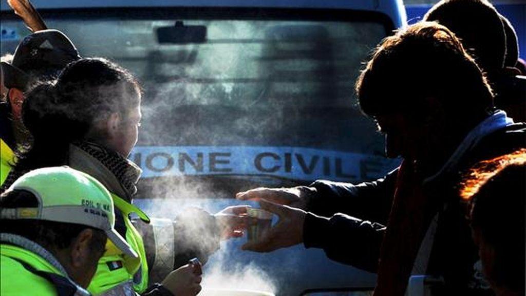 Un voluntario distribuye bebidas calientes entre los damnificados del terremoto en la localidad de Paganica (Italia) hoy miércoles 8 de abril. EFE