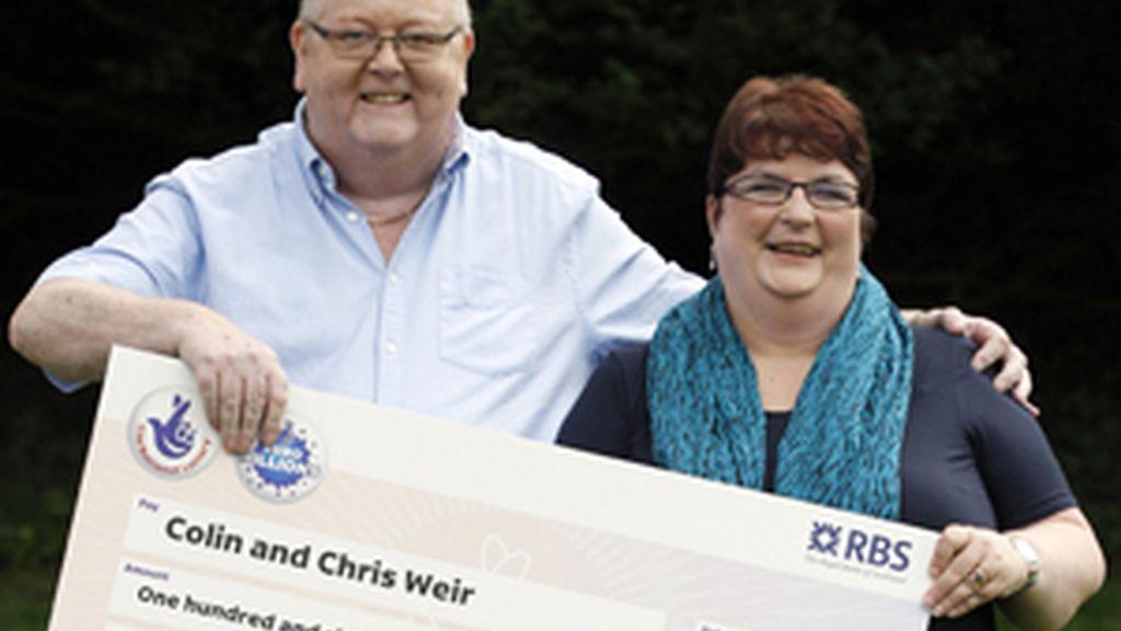 La pareja muestra feliz el cheque que les convierte en ganadores del premio