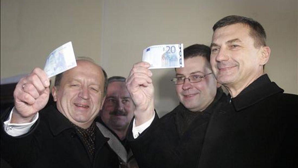 El primer ministro estoniano, Andrus Ansip (d), sostiene un billete de 20 euros junto al primer ministro de Letonia, Valdis Dombrovskis (2d), y su homólogo de Lituania Andrius Kubilius (i), durante la celebración del nuevo año hoy, sábado 1 de enero de 2011, en Tallin (Estonia), y tras convertirse en el decimoséptimo país de la Unión Europea que adopta el euro como su moneda. EFE