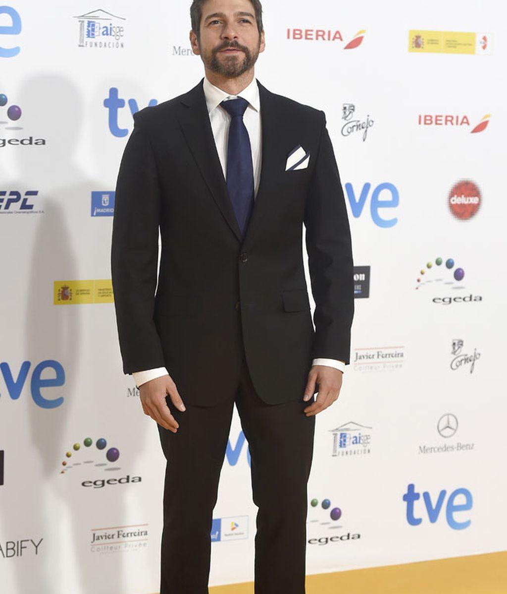 Félix Gómez con traje negro y corbata azul