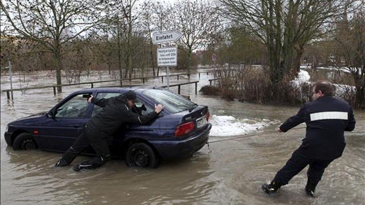 Los bomberos intentan saar un coche de en un parking inundado en Ansbach (Alemania) hoy, 8 de enero de 2011. Las lluvias y el deshielo producido por el alza de las temperaturas en Alemania provocaron hoy la subida del nivel del caudal de varios ríos, por lo que amenaza de inundaciones aumenta en estados como Hessen, Renania-Palatinado y Renania del Norte-Westfalia, oeste del país. EFE