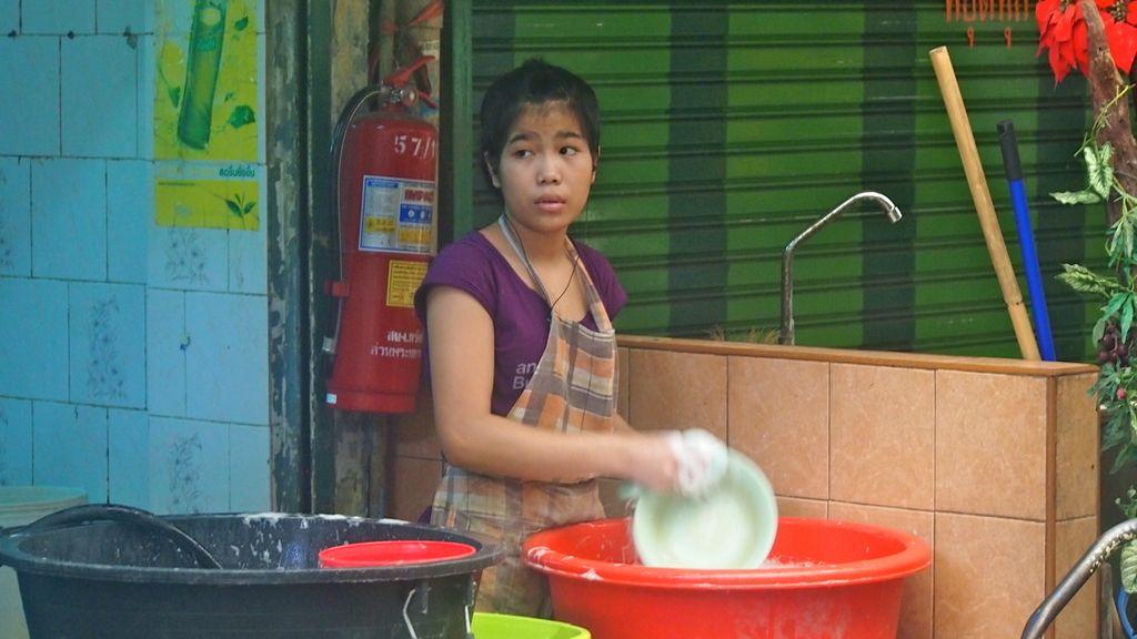 """Fregar platos en uno de los """"cien"""" puestos de Yawarat Road"""