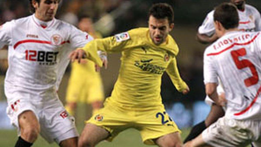 """Giuseppe Scurto """"Rossi"""" lucha por el balón ante los jugadores del Sevilla, Fernando Navarro y Luca Cigarini. Foto:EFE."""