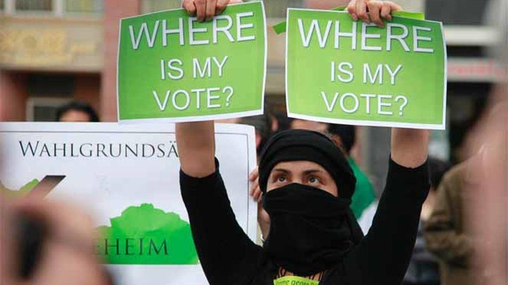 Un manifestante sostiene dos carteles durante una protesta en apoyo al ex candidato presidencial derrotado iraní Musavi en Francfort
