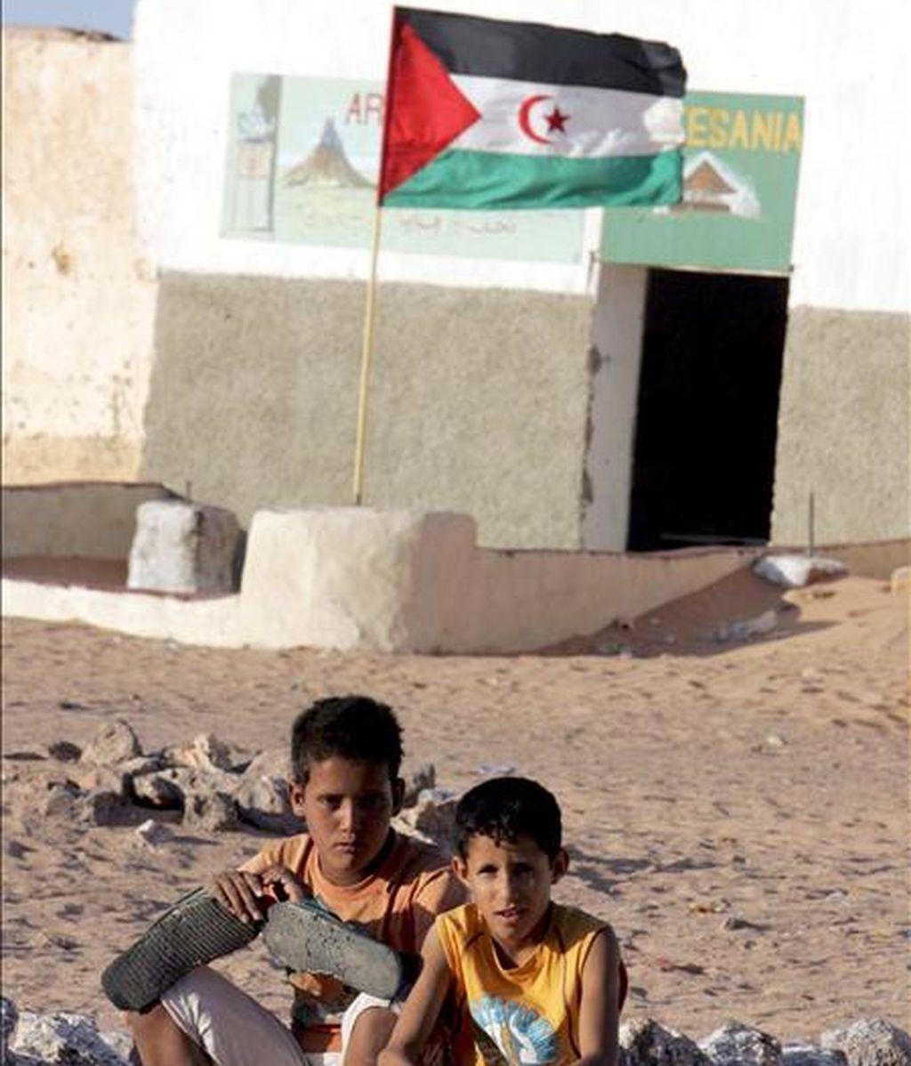Dos niños refugiados saharauis posan cerca de una bandera de la República Democrática Árabe del Sáhara al suroeste del desierto de Argelia. EFE/Archivo