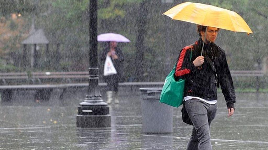 Un joven se resguarda bajo su paraguas de la fuerte lluvia