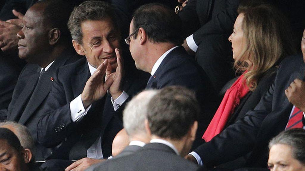 Francois Hollande y Nicolas Sarkozy conversan en las gradas