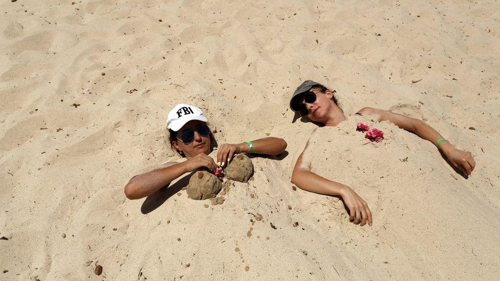 Dos turistas se dan un baño de arena en una playa de Túnez