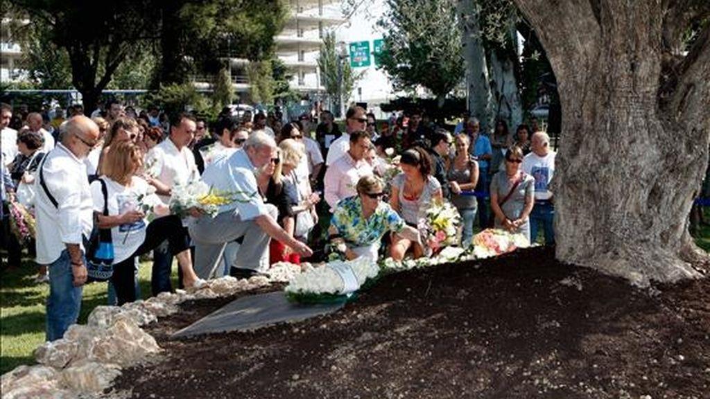 Miembros de la Asociación de Afectados del vuelo JK5022 depositando un ramo de flores junto al olivo en memoria de los fallecidos del avión de Spanair situado en el jardín de la T2 del aeropuerto de Barajas, en agosto de 2010. EFE/Archivo