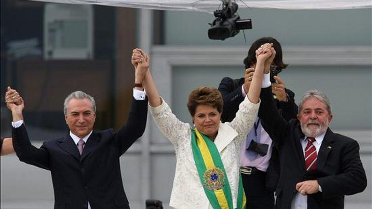 La nueva presidenta brasileña, Dilma Rousseff (c), recibe este 1 de enero en compañía de su vicepresidente Michel Temer (i), la banda presidencial de manos de su antecesor, Luiz Inácio Lula da Silva (d), en el Palacio de Planalto, en Brasilia (Brasil). EFE