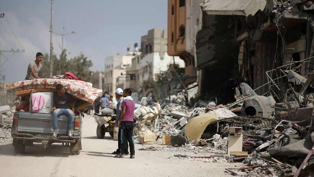 Los palestinos recogen sus provisiones y regresan a lo que queda de sus casas