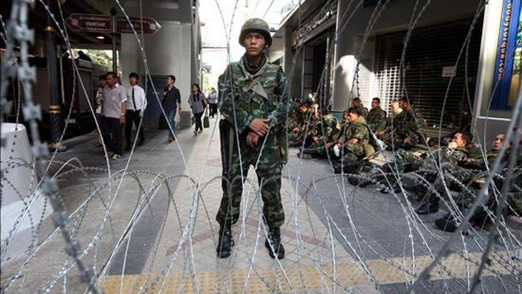 Trabajadores pasan junto a militares tailandeses armados hoy, en el distrito financiero de Bangkok (Tailandia) en donde tomaron posiciones para impedir que lo paralicen los miles de manifestantes antigubermanentales que exigen la disolución del Parlamento. EFE