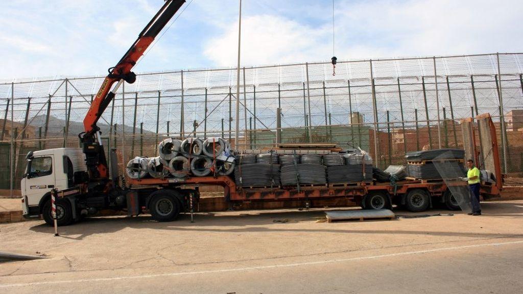 Operarios colocan los alambres con cuchillas en la valla de Melilla