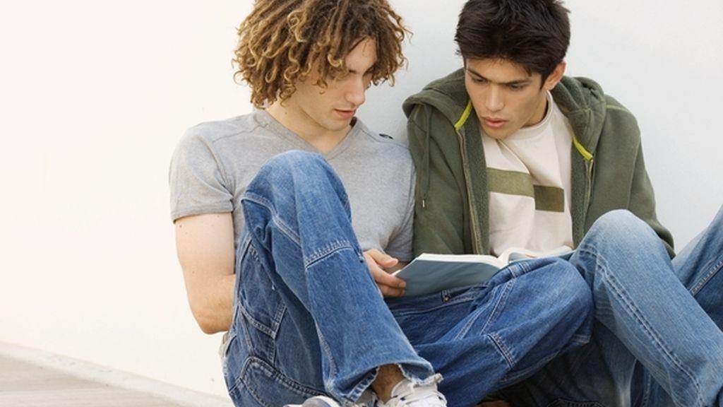 Dos jóvenes universitarios estudian juntos un manual