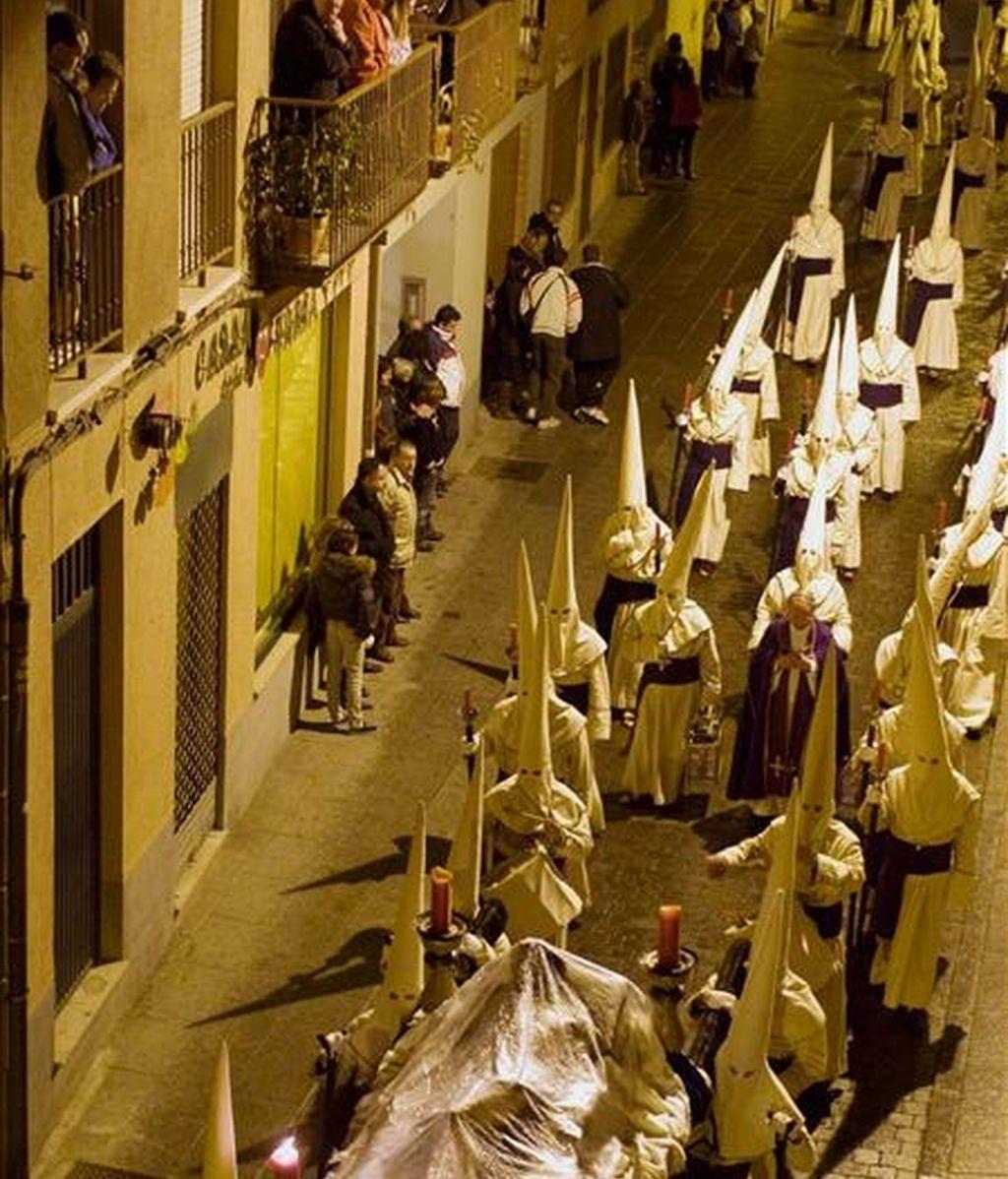 Cofrades de la Penitente Hermandad de Jesús Yacente acompañan a la talla de Jesús Yacente. EFE