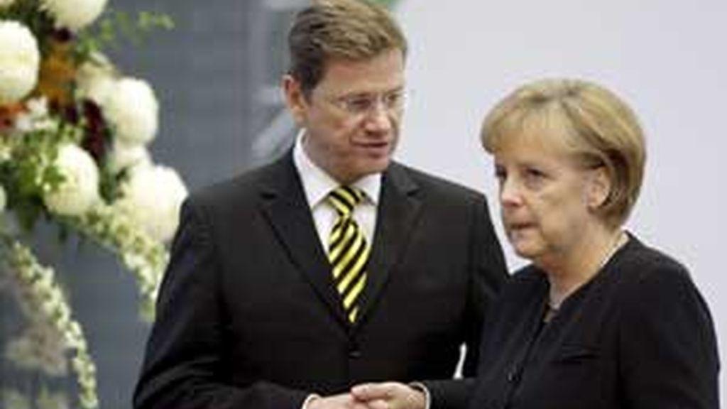 La canciller alemana, Angela Merkel, charla con el líder liberal Guido Westerwelle durante la última ronda de negociaciones para su nuevo gobierno de coalición, en Berlín. Foto: EFE