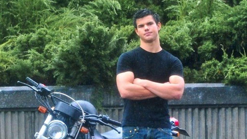 El sexy Taylor Lautner junto a su moto bajo la lluvia