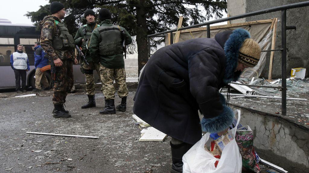 Mujer mirando una de las bolsas traídas por un convoy de ayuda humanitaria
