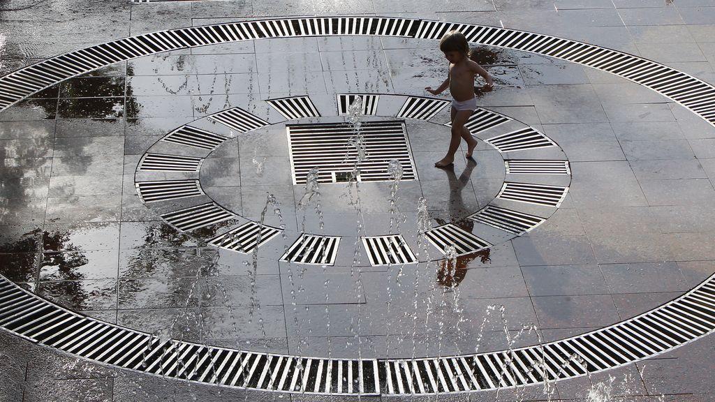 Un niño juega en una fuente en el centro de Kiev