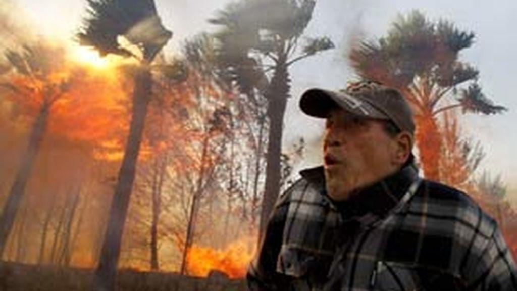 Un vecino intenta acceder a su casa incendiada en el municipio de La Nucia. Foto: EFE.