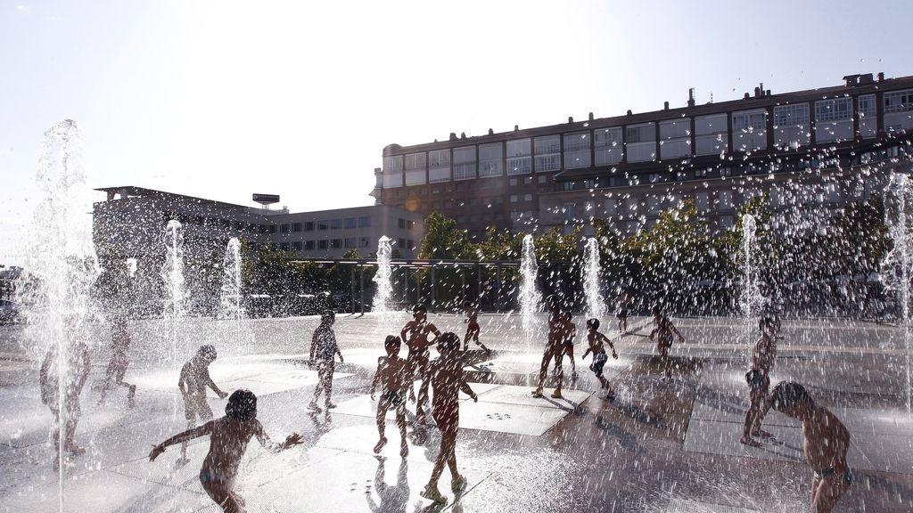 Un grupo de niños se refrescan en una fuente del parque Yamaguchi, en Pamplona
