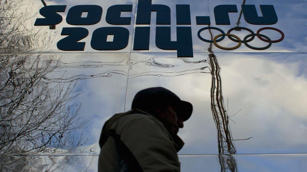 Hombre pasa junto a logotipo olímpico en Sochi (Rusia)