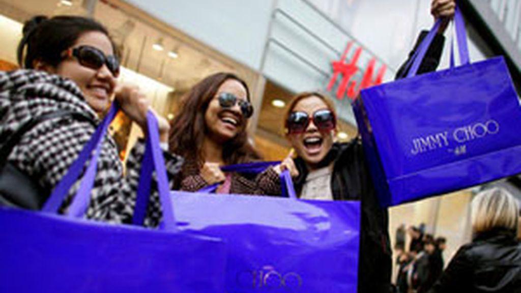 Varias compradoras muestran entusiasmadas sus adquisiciones de Jimmy Choo. Foto: EFE