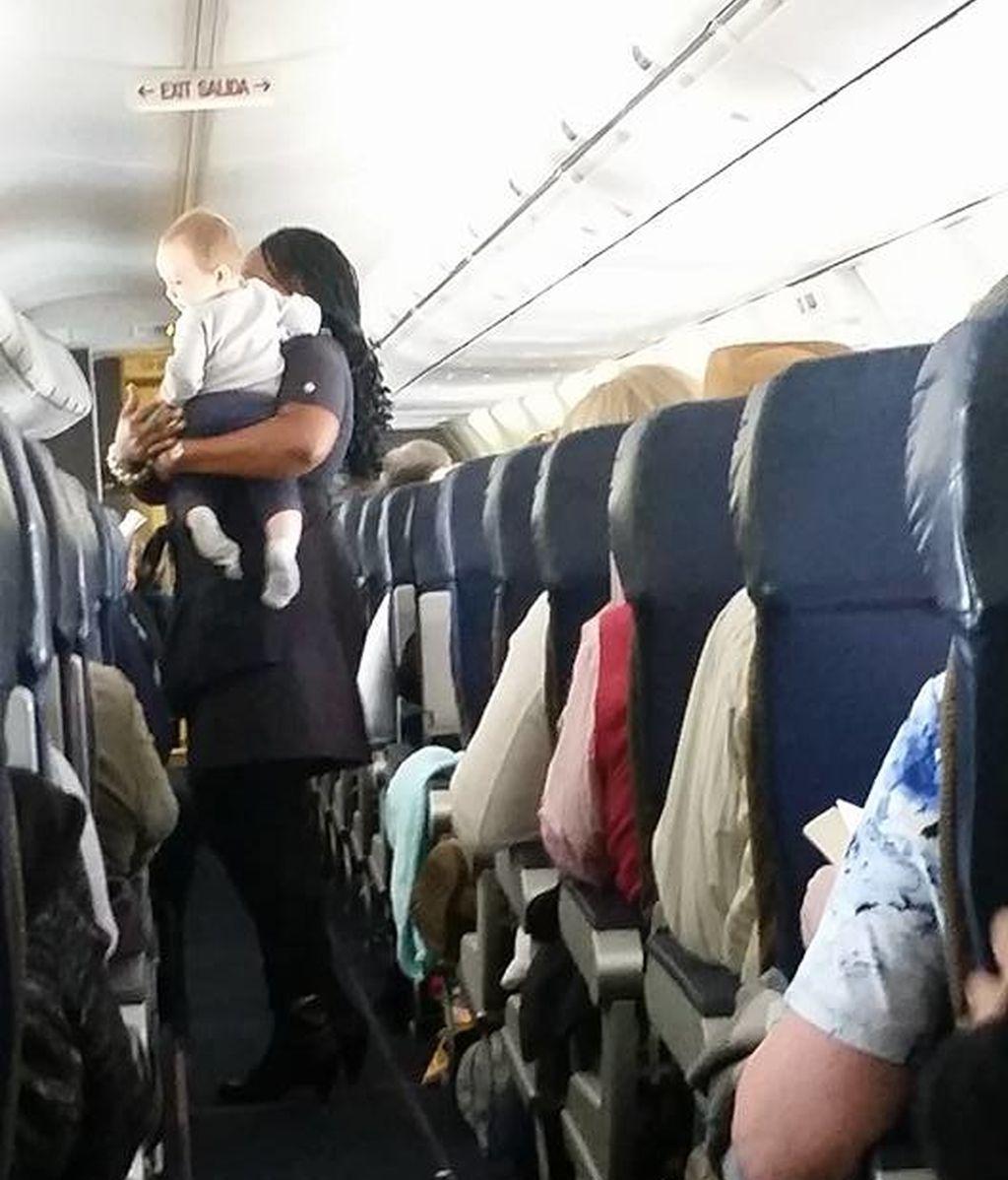 Azafata calma a un niño durante el vuelo