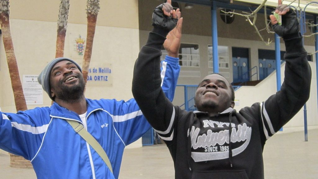 Dos inmigrantes celebran haber pasado la frontera de Melilla