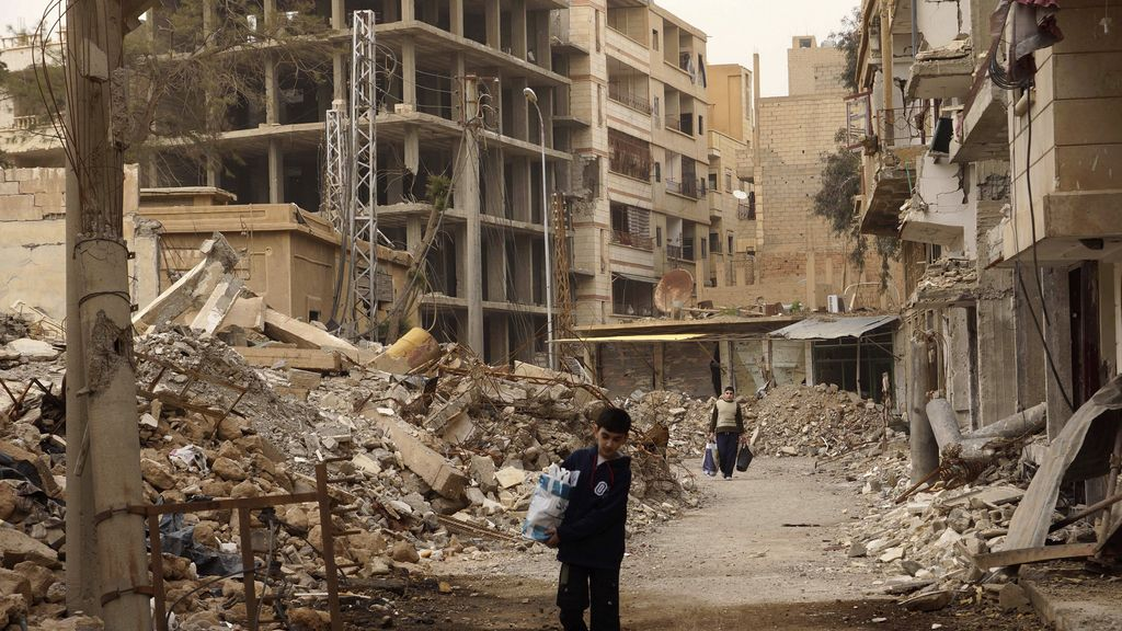 Ciudadanos sirios con sus pertenencias en calles desiertas y destruidas por la guerra