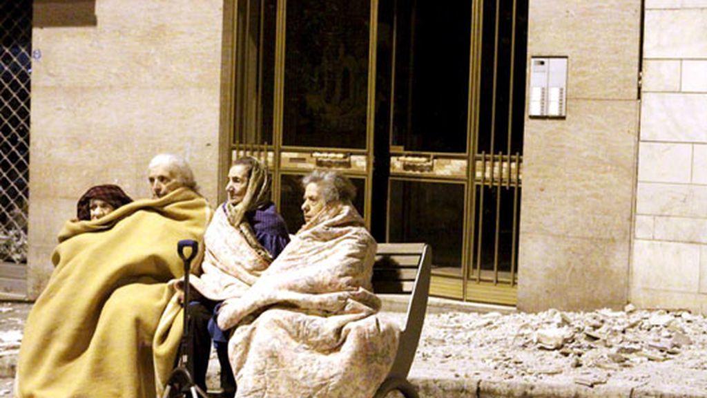 Cuatro ancianas junto a los escombros provocados por el terremoto