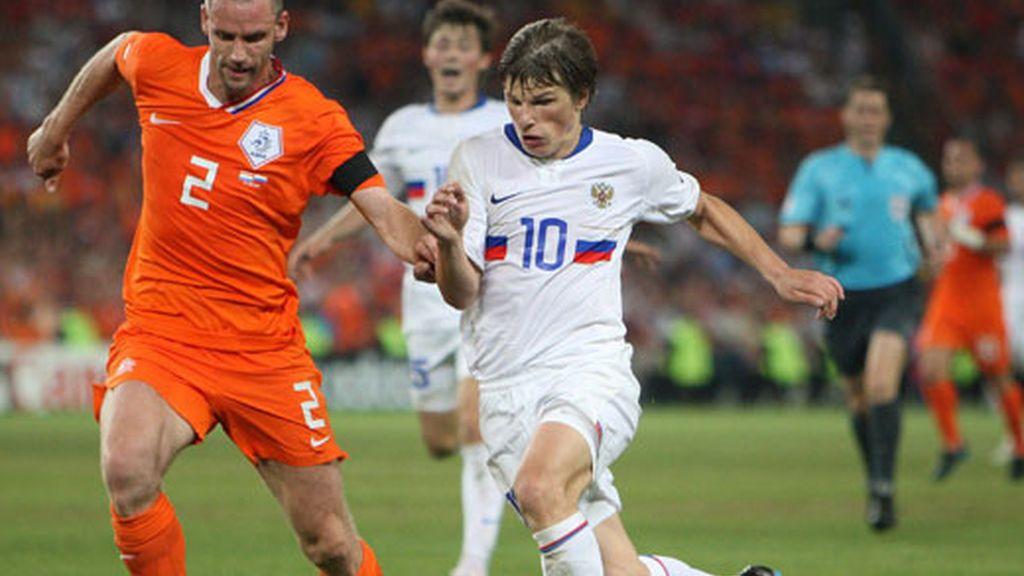 El holandés Andre Ooijer (i) disputa el balón con el ruso Andrei Arshavin (d)