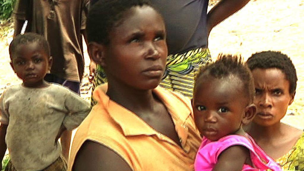 Una mujer porta en brazos a su niña pequeña