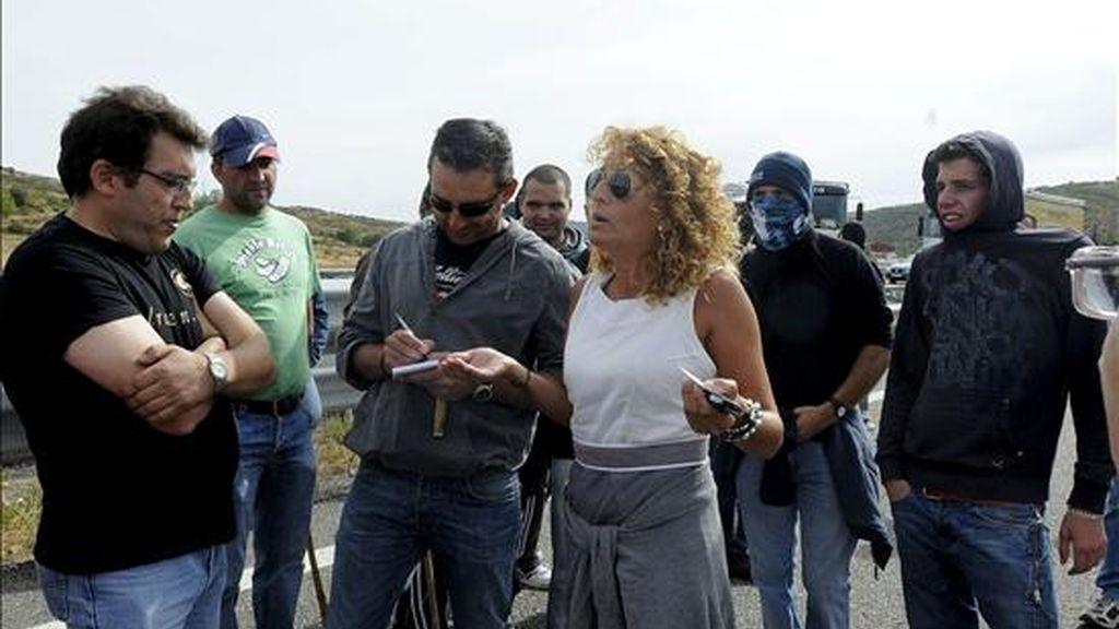 Una mujer conversa con varios de los trabajadores de la minería en la provincia de León, que esta mañana han cortado la AP-66, a la altura de La Magdalena. Las autopistas AP-66 (León-Campomanes) y la A-6 (Madrid-A Coruña) están abiertas al tráfico, después de que se hayan levantado los cortes.EFE
