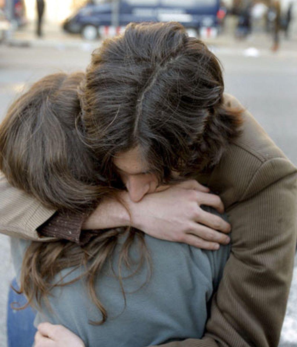 Una pareja se abraza frente a la Universidad