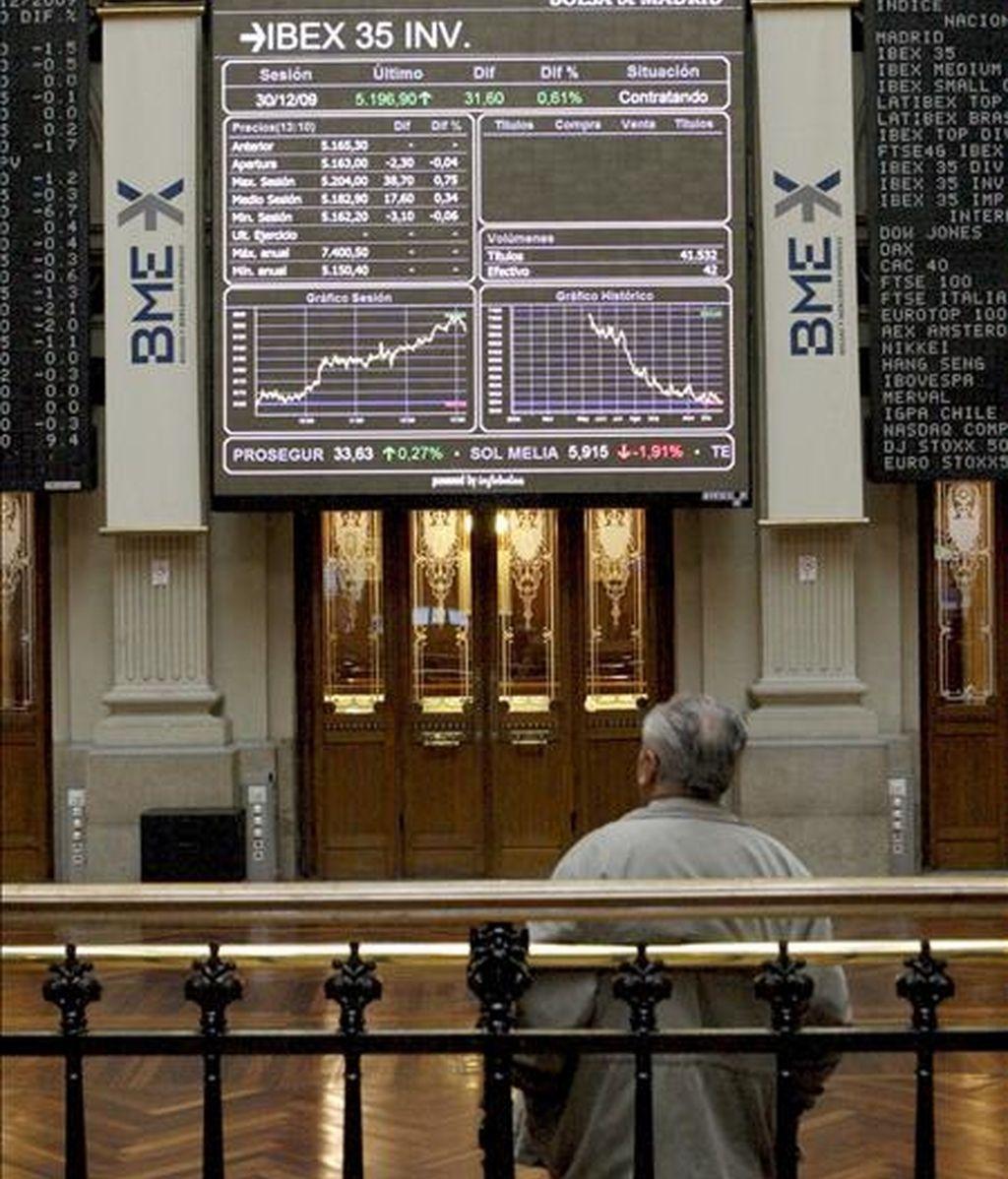 Un inversor contempla hoy un panel de cotizaciones en la Bolsa de Madrid, mercado que cierra el año con una revalorización cercana al 31%. EFE