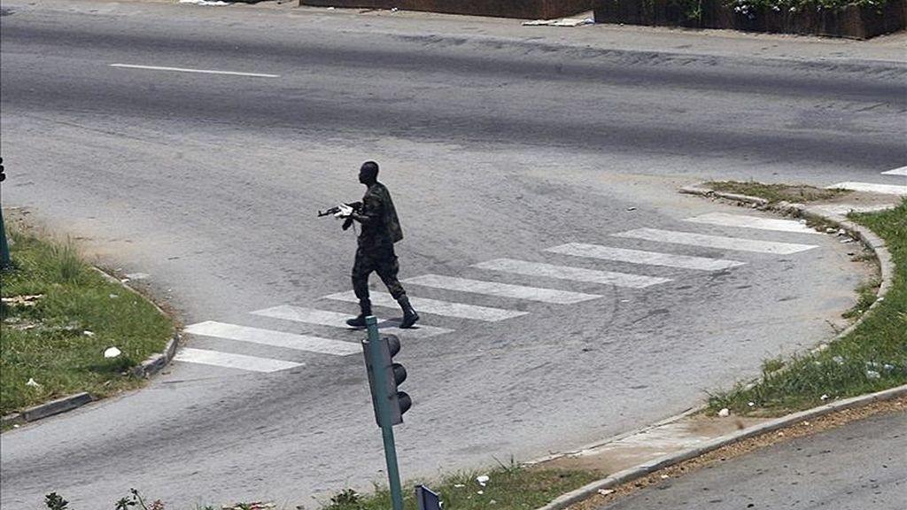 """Un soldado leal al presidente Laurent Gbagbo cruza una calle de Abiyán, Costa de Marfil. Oficiales partidarios de Gbagbo instaron hoy, a través de la televisión pública, a la movilización de sus tropas """"para proteger las instituciones de la República"""". EFE"""