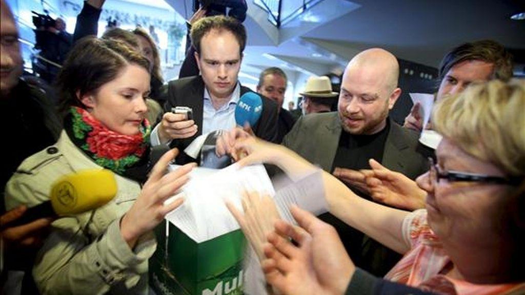 """Varios periodistas cogen copias de la sentencia del caso """"The Pirate Bay"""", en un tribunal de Estocolmo (Suecia), hoy, 17 de abril. Los cuatro responsables del portal de Internet sueco """"The Pirate Bay"""" fueron condenados a un año de cárcel y al pago de una indemnización de 30 millones de coronas (2,7 millones de euros) por violar los derechos de propiedad intelectual. EFE"""