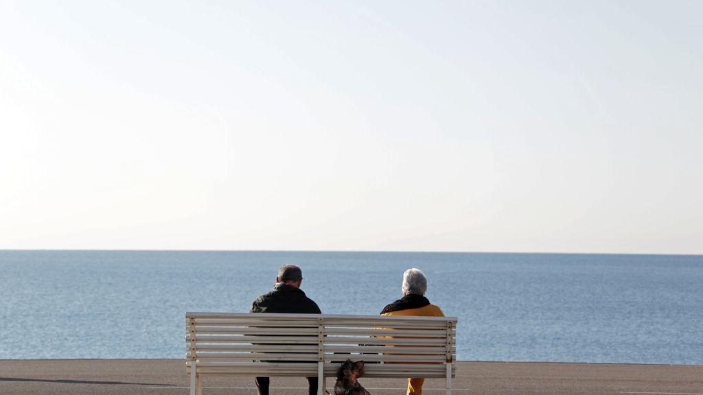 Una pareja sentada ante el mar