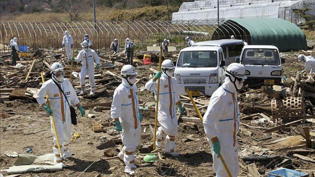 La policía japonesa vestida con trajes de seguridad nuclear buscan víctimas del terremoto y posterior tsunami del 11 de marzo de 2011.