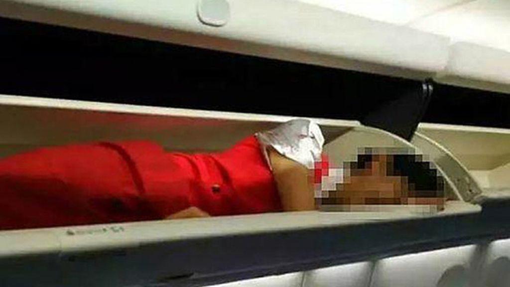 Azafata dentro de un compartimento de maletas