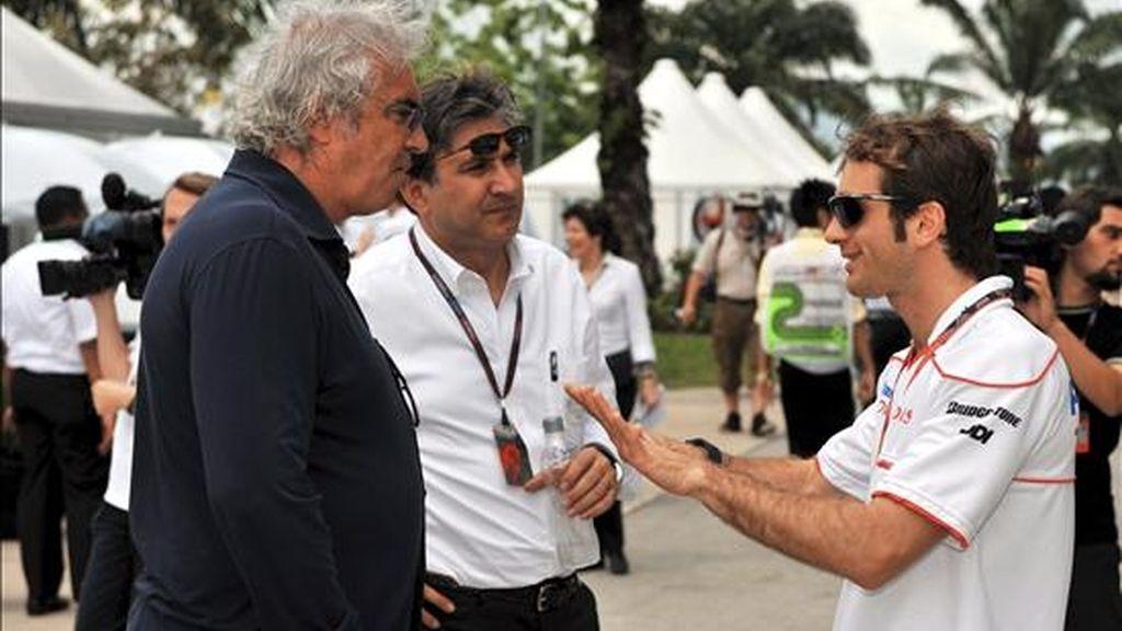 El piloto de Fórmula Uno Jarno Trulli (d), de Toyota, habla con el director de la escudería Renault, Flavio Briatore (i), y con un hombre no identificado, hoy en el circuito de Sepang (Malasia). EFE