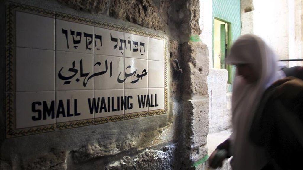 Una mujer palestina camina por el callejón que da entrada al Pequeño Muro de la vieja ciudad de Jerusalén, Israel. EFE/Archivo